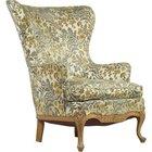 Un sillón de orejas clásico está acolchado por todas partes con patas delanteras curvas.