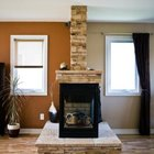In this unusual brick surround design, the brick chimney extends all the way to the ceiling.