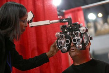 An optometrist giving an eye exam in a clinic.