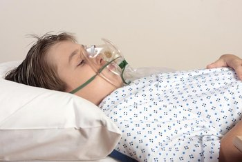 Young boy in hospital bed wearing an oxygen mask.