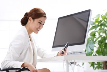 A woman sitting in front of an iMac.