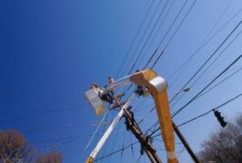 Journeymen linemen use special equipment to fix electrical boxes on utility poles.