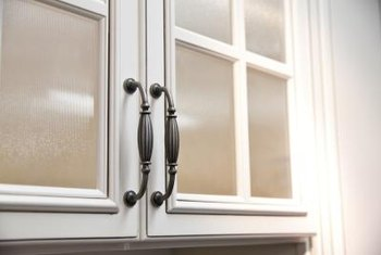 Never underestimate the change new, or even spray painted, hardware can make on older kitchen cabinets.