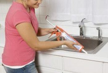 Kitchen and bathroom sinks are adhered with silicone caulk to fasten the sink and create a watertight barrier.