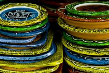 Stack colorful plates on the shelves of a hutch for decorative storage.