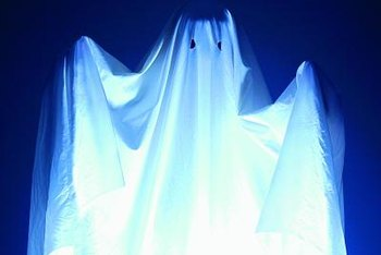 Fabric or an old sheet is used to create a hanging ghost.