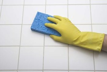 Wear rubber gloves while you clean mildew off tiles.