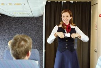 Flight attendants demonstrate an airplane's safety feautures before a flight leaves the airport.