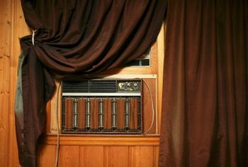 Drapes will hide an AC unit, especially if it is mounted below a window.