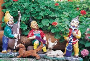 Geraniums provide a colorful backdrop to the gnome band.