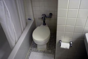 A toilet in a cramped area makes the bathroom look small.