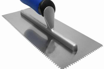 A trowel has a notched edge and a flat edge for working thinset.