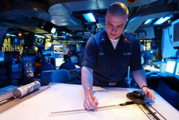 U.S. Navy operations specialists work in combat information centers.