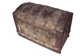 An antique steamer trunk provides storage for blankets in a bedroom.