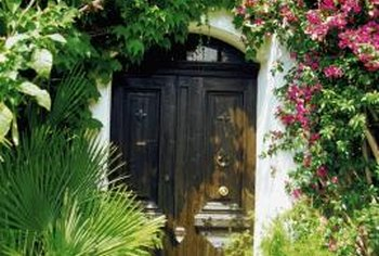 Both French and Italian style emphasize gardens and colorful flowers, like these around an arched doorway in Vence, Provence.