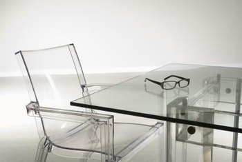 A glass table with Lucite chairs and a sleek metal base nearly disappears in the minimalist or monochromatic space.