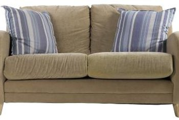 A khaki sofa is accented by striped denim pillows.