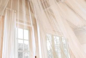 Tulle can form a bed canopy when mounted to the ceiling with a ring.