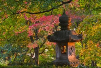 Asian sculpture and flowering trees are elements of a soothing Japanese garden.