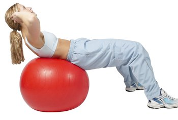 Bend your knees to perform exercise-ball crunches.