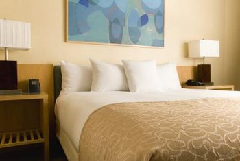 A contemporary painting creates a focal point on this bedroom wall.