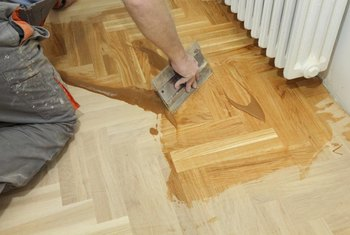 A worker adds a tinted low-gloss varnish to this oak parquet floor.