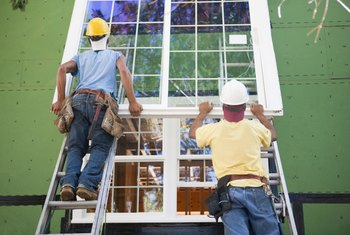 Construction workers installing new windows on a house