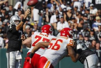 Oakland quarterback Kyle Boller lobs a screen pass over Kansas City pass rushers.