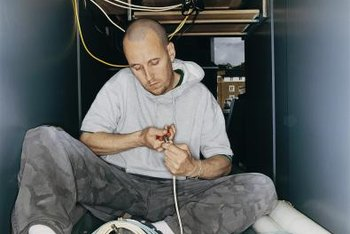 Electricians must sometimes handle tasks in cramped quarters.