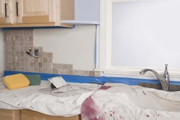 Painter's tape and a drop cloth protect the cabinets and countertop from thinset and grout.