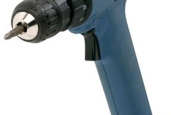 A cordless drill is used when installing a wooden screen door.