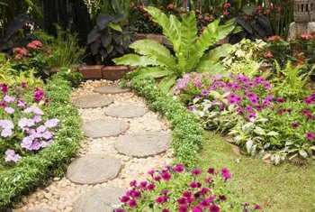 Winding stone pathways bordered by ornamental plants or herbs create an alluring backyard garden.