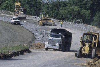 Highway construction workers use large vehicles and equipment.
