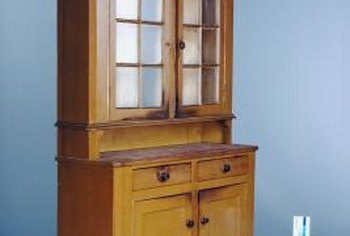 Distressing and glazing your stained cabinet will make it look older.