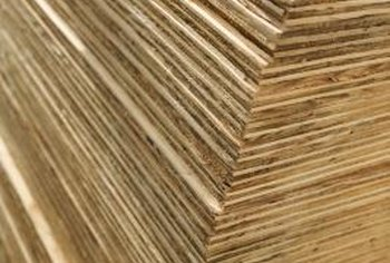 Thin sheets of wood glued together under pressure produce plywood sheets.