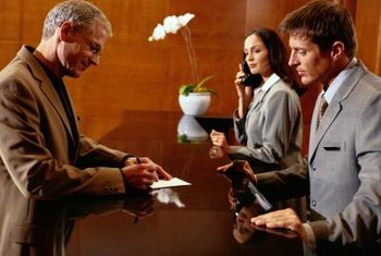 Hotel receptionists greet guests and handle guest room assignments.