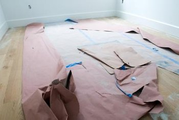 A combination of plastic sheeting and kraft paper or foam board will protect your floors.