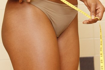 Use a tape measure to track your waist, hip, thigh and arm measurements.