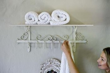 Budget-friendly open shelves and hooks can help to quickly update a master bathroom.